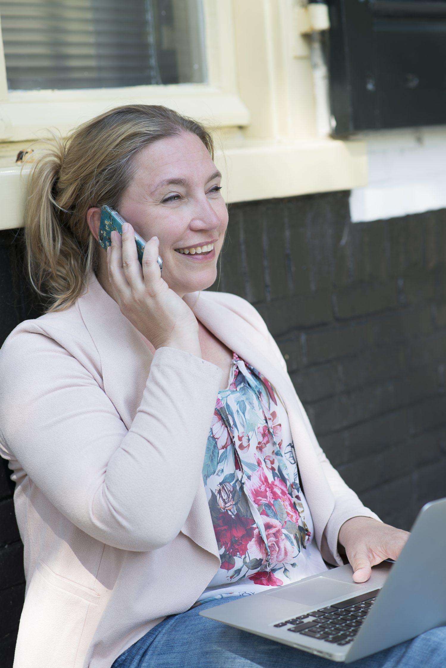 Lachende vrouw met mobiel en laptop: Pauli Venekamp communicatieadviseur